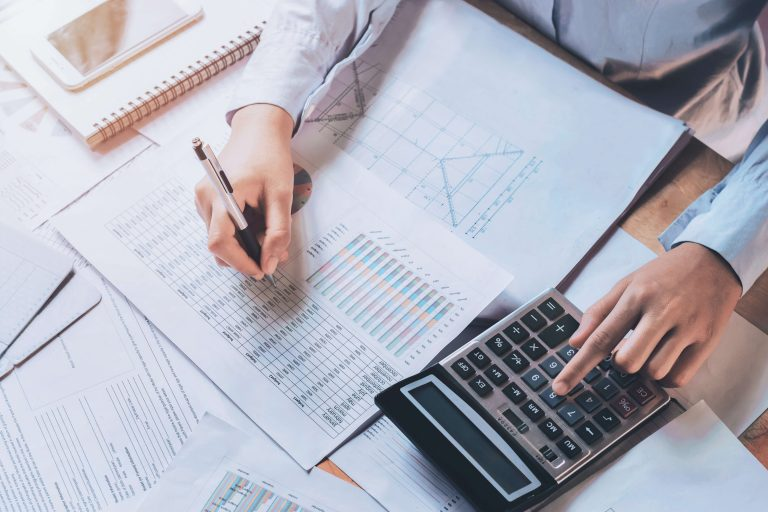 calculating finances using calculator, pen, and paper