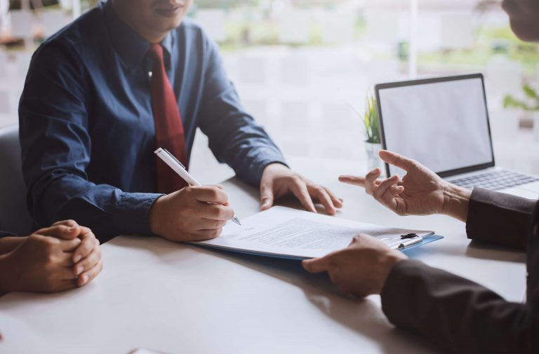 three people at a table talking about a business contract