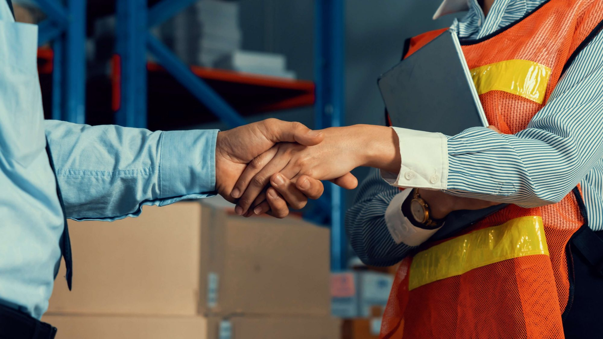 man in tie shakes hands with woman in woman in orange vest in supply room